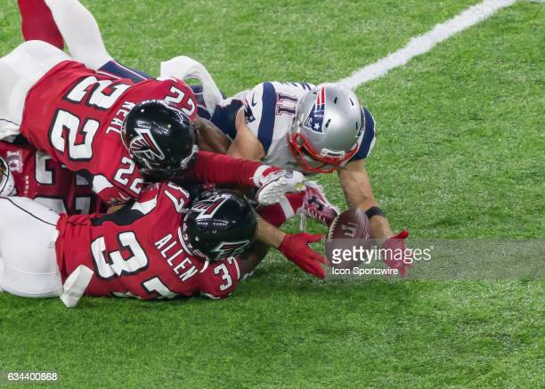 New England Patriots wide receiver Julian Edelman is tackled by Atlanta Falcons strong safety Keanu Neal and Atlanta Falcons free safety Ricardo...