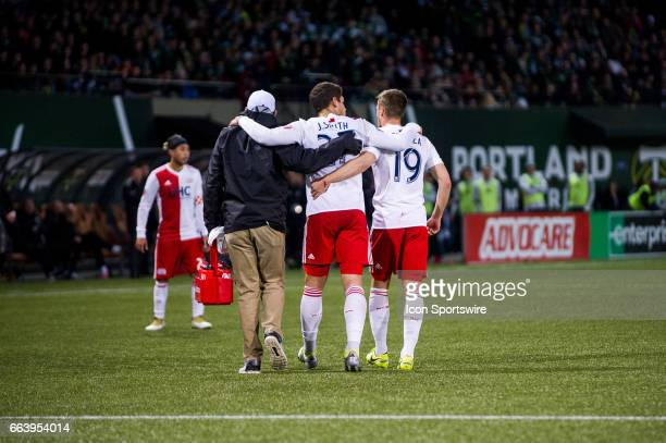 New England Revolution defender Joshua Smith is helped off the pitch by medical staff and also defender Antonio Mlinar Delamea in injury time during...