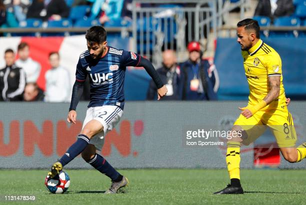 New England Revolution forward Carles Gil back heels away from Columbus Crew midfielder Artur during a match between the New England Revolution and...