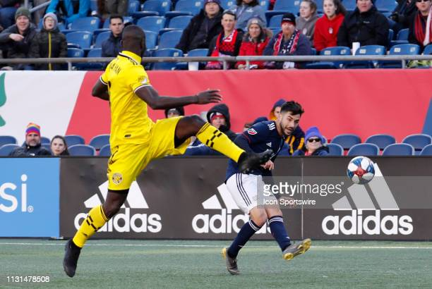 New England Revolution forward Carles Gil bends the pass around Columbus Crew defender Jonathan Mensah during a match between the New England...