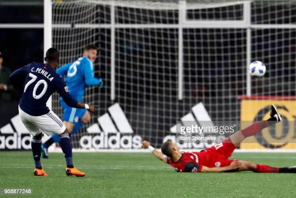 New England Revolution forward Cristian Penilla watches his second goal of the match beat Toronto FC defender Jason Hernandez and Toronto FC...