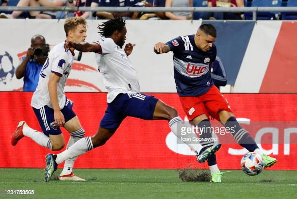 New England Revolution forward Gustavo Bou hits a cross as DC United defender Chris Odoi-Atsem and DC United forward Griffin Yow move in during a...