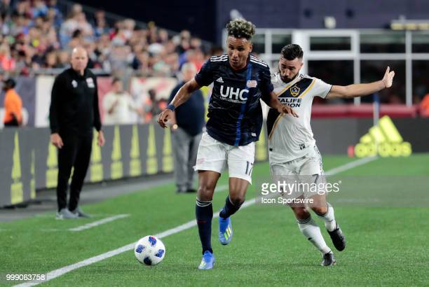 New England Revolution forward Juan Agudelo edges off Los Angeles Galaxy midfielder Romain Alessandrini during a match between the New England...