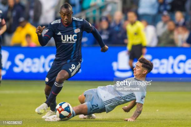 New England Revolution forward Juan Caicedo leaps over the attempts slide tackle of Sporting Kansas City midfielder Felipe Gutierrez during the match...