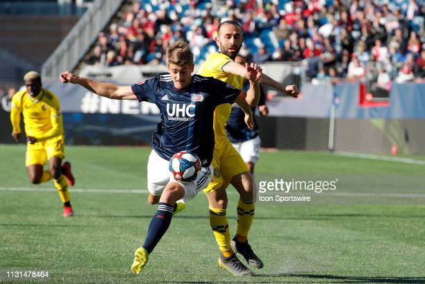 New England Revolution forward Justin Rennicks gets past Columbus Crew midfielder Justin Meram during a match between the New England Revolution and...