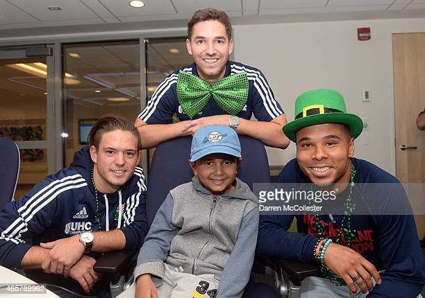 New England Revolution Kelyn Rowe Tyler Rudy and Charlie Davies visit with Abdullrahman at Boston Children's Hospital March 10 2015 in Boston...