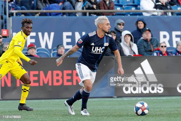 New England Revolution midfielder Diego Fagundez looks for an open teammate watched by Columbus Crew defender Harrison Afful during a match between...