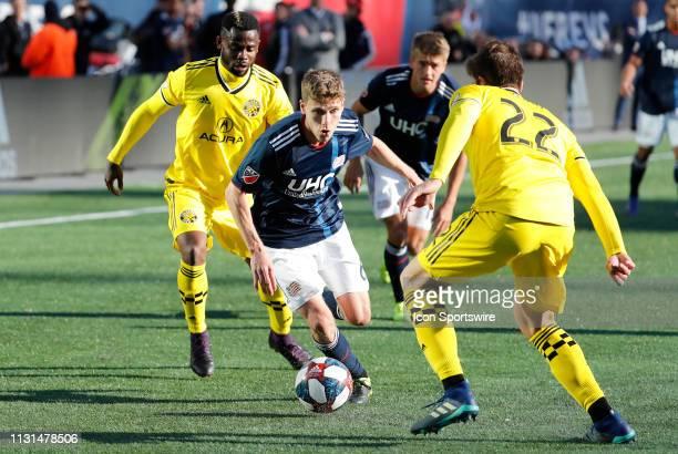 New England Revolution midfielder Scott Caldwell tries to get through Columbus Crew defender Gaston Sauro during a match between the New England...