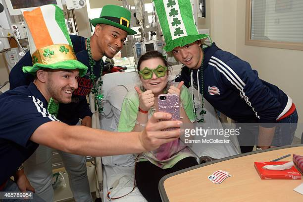 New England Revolution Tyler Rudy Charlie Davies and Kelyn Rowe take a selfie with Belle at Boston Children's Hospital March 10 2015 in Boston...