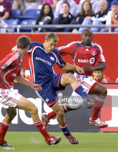 New England Revolution's Adam Cristman splits Toronto FC' Andrew Boyens left and Marvell Wynne during MLS action at Gillette Stadium in Foxborough MA...