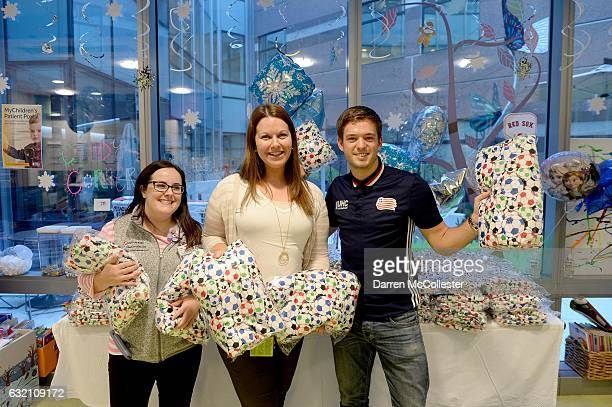 New England Revolutions Kelyn Rowe and Boston Children's Hospital Child Life Specialists Annika Stout and Brittany Metcalfe prepare to hand out...