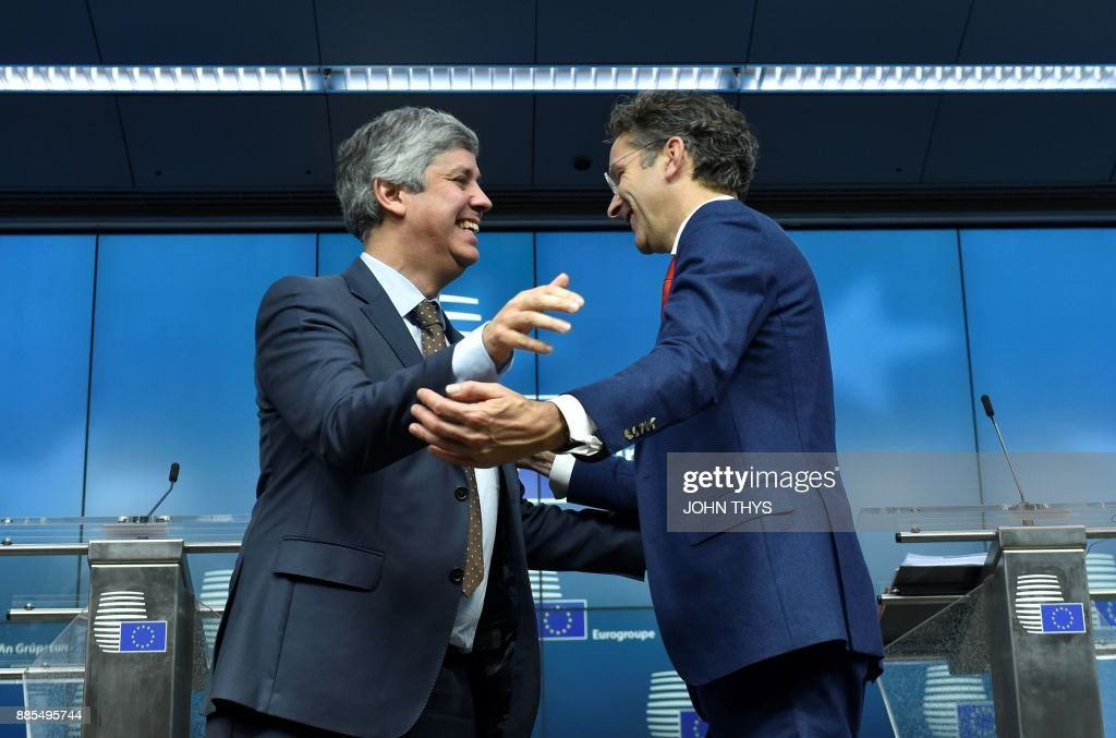 New Eurogroup President Portuguese Finance Minister Mario Centeno (L) is congratulated by former Dutch Finance Minister and parting Eurogroup president Jeroen Dijsselbloem following a press conference on his election as new Eurogroup chief at the European Council in Brussels on December 4, 2017. The 50-year-old economics professor who is often called a liberal but sees himself 'culturally of the left' accedes to the top post among eurozone finance ministers after only two years in politics. /