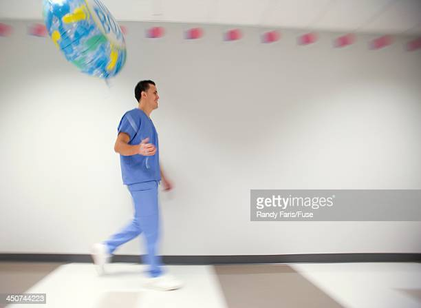 New Father in Hospital Hallway with Balloon