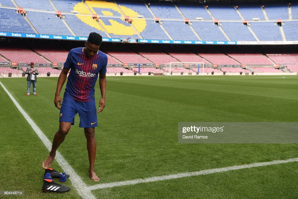 New FC Barcelona player Yerry Mina takes off his boots before walking on the pitch as he is unveiling at Nou Camp on January 13, 2018 in Barcelona, Spain. The Colombian player signed from Palmerias, has agreed a deal with the Catalan club until 2022 season.