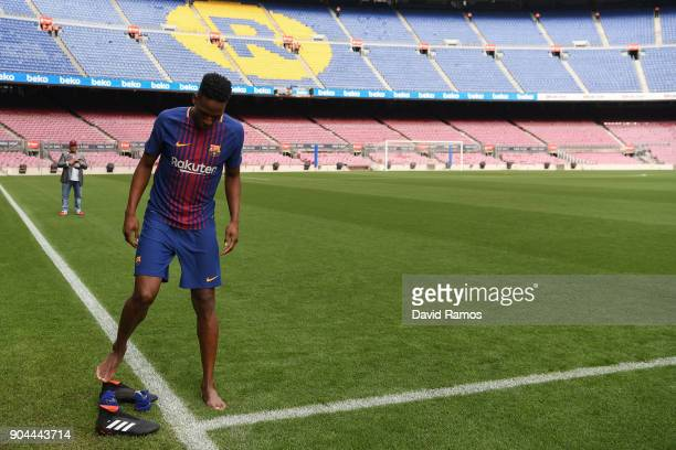 New FC Barcelona player Yerry Mina takes off his boots before walking on the pitch as he is unveiling at Nou Camp on January 13 2018 in Barcelona...