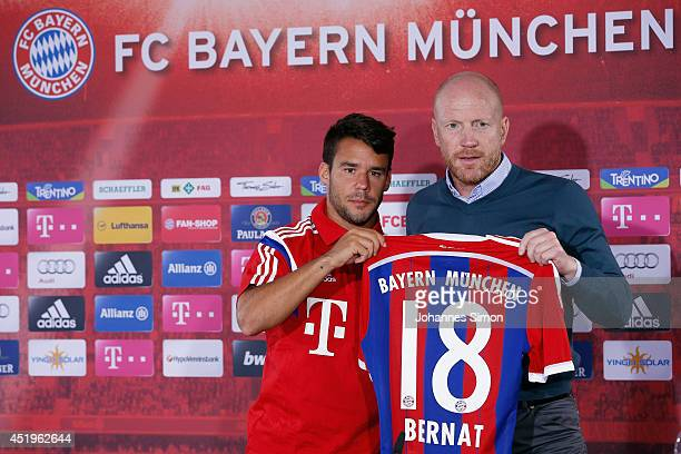 New FC Bayern Muenchen player Juan Bernat and sporting manager Matthias Sammer hold up Bernat's new jersey during his presentation to the media at...