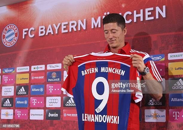New FC Bayern Muenchen player Robert Lewandowski looks at his new jersey during his presentation at the Bayern Muenchen training ground on July 9...