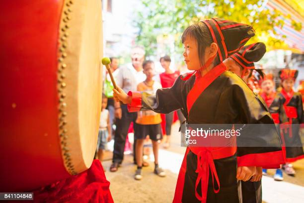 A new firstgrader beats a drum during a first writing ceremony at a temple on August 30 2017 in Foshan Guangdong Province of China 72 new...
