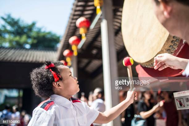 A new firstgrader beats a drum during a first writing ceremony on August 30 2017 in Guangzhou Guangdong Province of China Firstgraders get red dots...