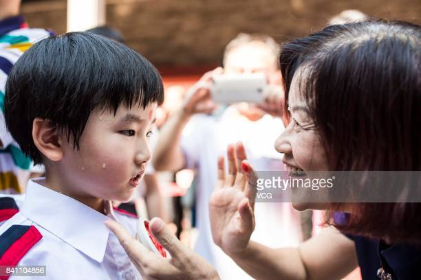 A new firstgrader gets a red dot on forehead during a first writing ceremony on August 30 2017 in Guangzhou Guangdong Province of China Firstgraders...