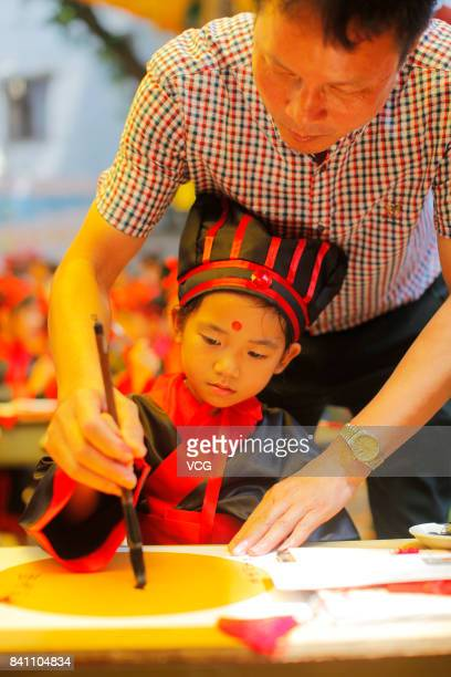 A new firstgrader writes calligraphy during a first writing ceremony at a temple on August 30 2017 in Foshan Guangdong Province of China 72 new...