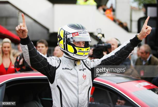 New Formula One World Champion Jenson Button of Great Britain and Brawn GP prepares to take competition winners for a drive following a Virgin...