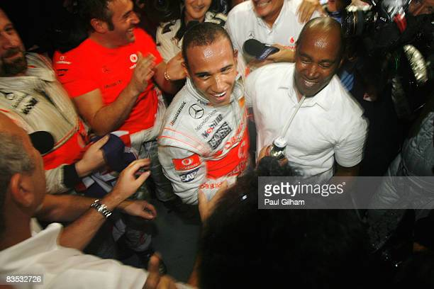 New Formula One World Champion Lewis Hamilton of Great Britain and McLaren Mercedes celebrates with his father Anthony Hamilton and his Team...