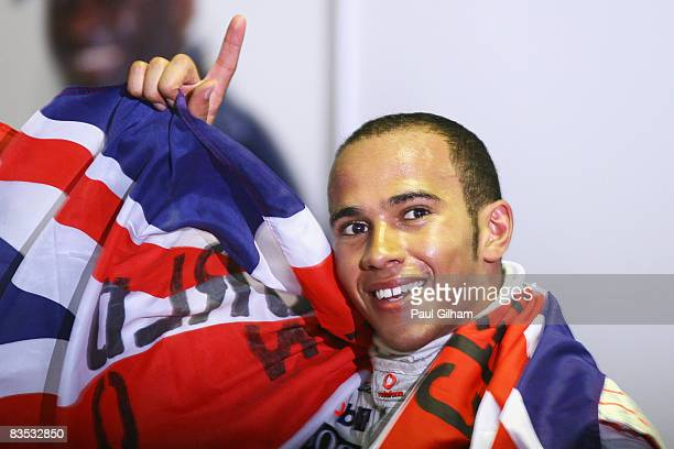 New Formula One World Champion Lewis Hamilton of Great Britain and McLaren Mercedes celebrates in his team garage following the Brazilian Formula One...