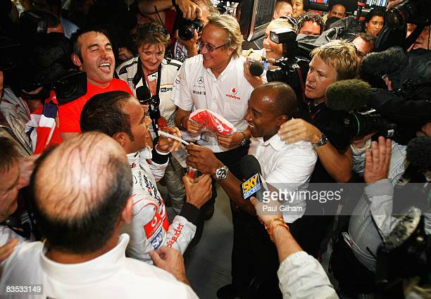 New Formula One World Champion Lewis Hamilton of Great Britain and McLaren Mercedes celebrates with his father Anthony Hamilton and Mansour Ojjeh of...