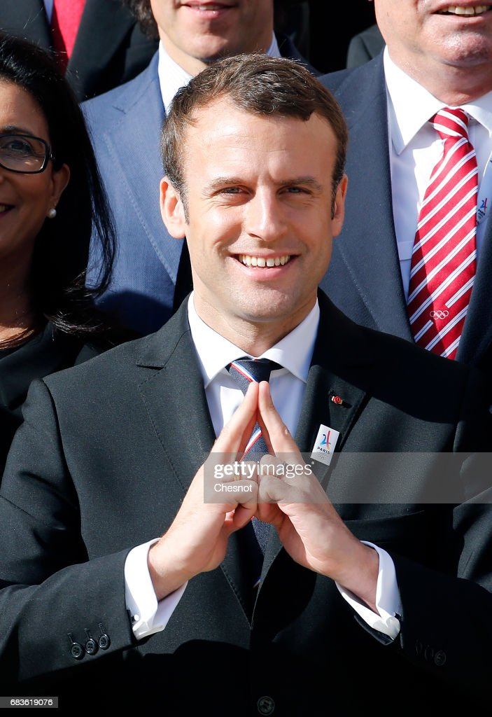 New French President Emmanuel Macron makes a sign representing the Eiffel Tower, the logo of Paris 2024 bid as he poses during a family photo with members of the International Olympic Committee (IOC) Evaluation Commission at the Elysee Presidential Palace in Paris, France, May 16, 2017. The cities of Paris and Los Angeles are currently bidding to host the 2024 Olympic Game.