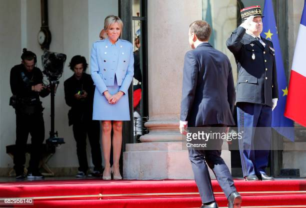 New French President Emmanuel Macron walks back along the red carpet after escorting outgoing French President Francois Hollande as his wife Brigitte...