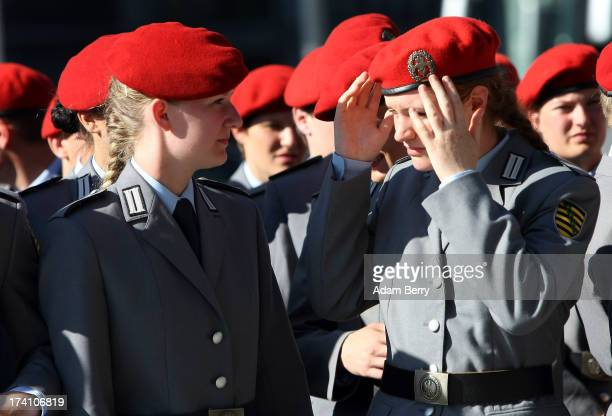 A new German Bundeswehr soldier adjusts her hat prior to the start of a swearingin ceremony for new recruits of the Bundeswehr the armed forces of...