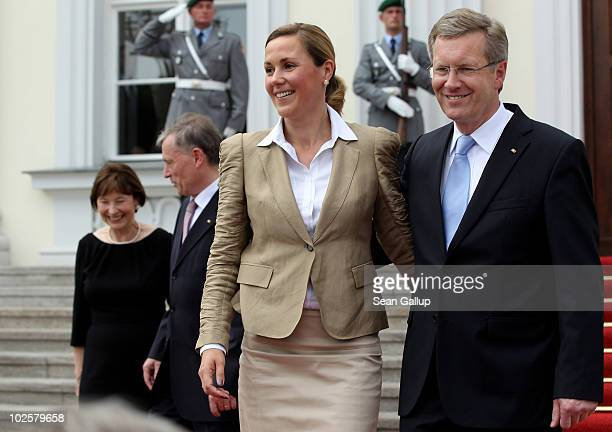 New German President Christian Wulff and his wife First Lady Bettina Wulff pose at the entrance to Schloss Bellevue presidential palace after Wulff...