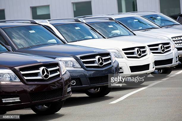 new glk-class mercedes vehicles in a row at car dealership - mercedes stock photos and pictures