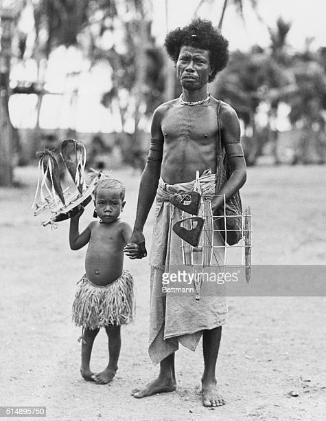 New Guinea types Man and child holding model boats