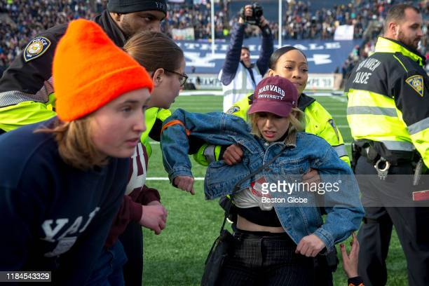 New Haven police officer lifts a student up during the protest during the halftime of the college football game between Harvard and Yale at the Yale...