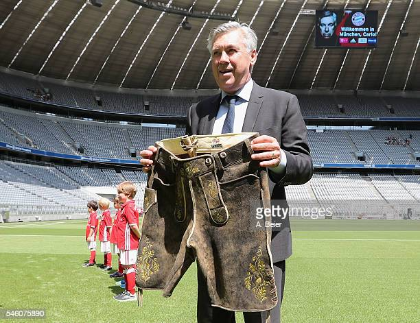 New head coach of FC Bayern Muenchen Carlo Ancelotti poses with a traditional Bavarian leather trousers he received as present during his first visit...