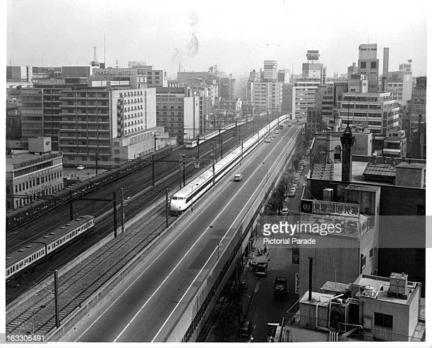 New high speed express train called 'Hikari' is traveling down the railroad tracks parallel to the highway in Tokyo Japan 1955
