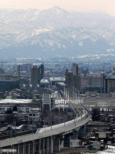 A new Hokuriku 'shinkansen' or bullet train runs in front of the Tateyama peaks after leaving the main station in Toyama in Toyama prefecture on...