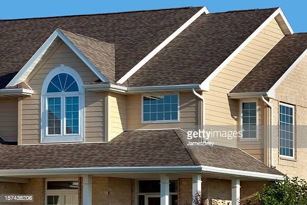 new home exterior; house with architectural asphalt roof, vinyl siding - roof stock photos and pictures