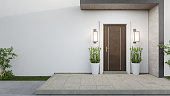 New house with wooden door and empty white wall.