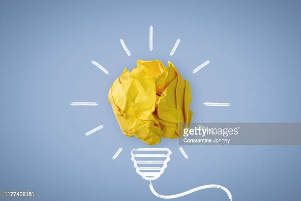 new idea. crumpled paper ball glowing bulb concept. - inspiratie stockfoto's en -beelden