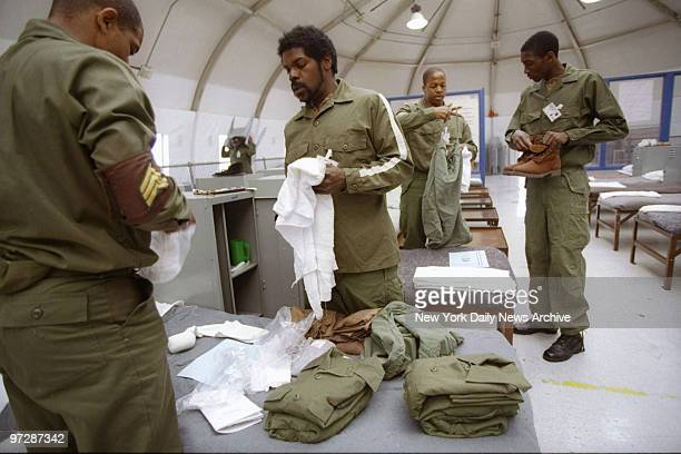 New immate Leslie Hipp gets help on how to fold his clothes from more experienced inmates who are members of the High Impact Incarceration Program at...