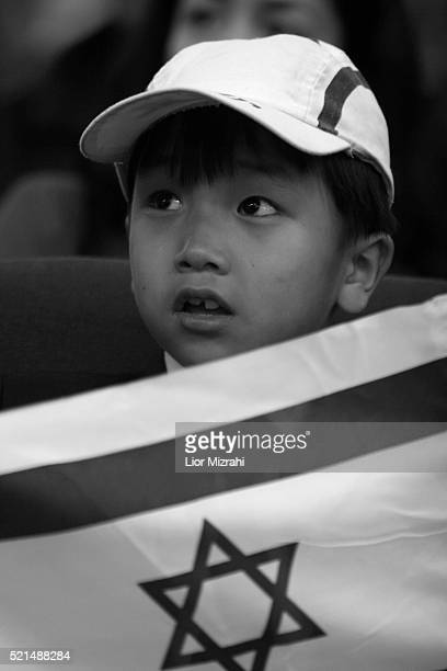 A new immigrant boy from the 'Bnei Menashe' tribe holds an Israeli flag after arrives in Ben Gurion International Airport in Lod as they emigrate...