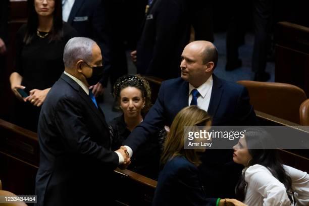 New Israeli Prime Minister Naftali Bennettut shakes hands with outgoing Israeli Prime Minister Benjamin Netanyahu looks on after parliament voted to...
