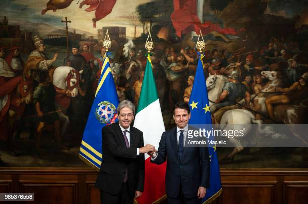 New Italian Prime Minister Giuseppe Conte receives a silver bell from former Prime Minister Paolo Gentiloni during the swearingin ceremony at the...