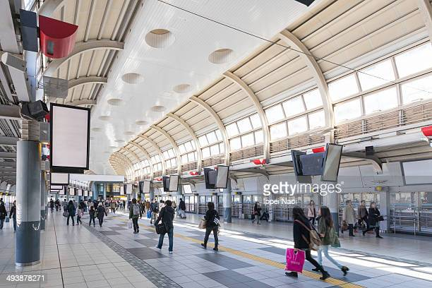 CONTENT] New Japanese train station undercover walkway with advertising boards and pedestrians Shinagawa Tokyo Japan