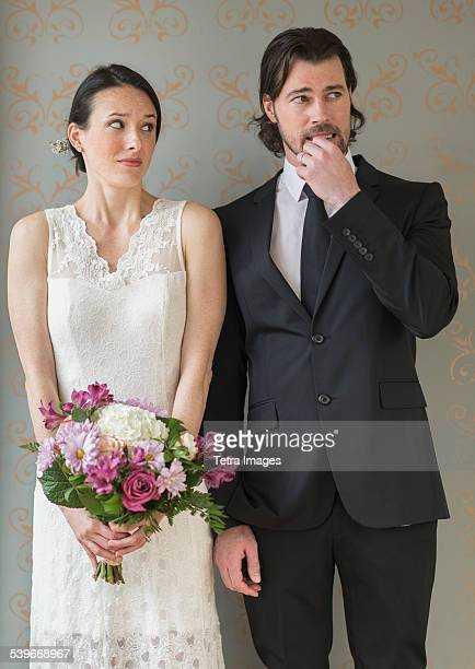 USA, New Jersey, Anxious bride and groom posing with bunch of flowers