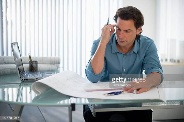 usa, new jersey, architect with blueprints in office - rolled up sleeves stock photos and pictures