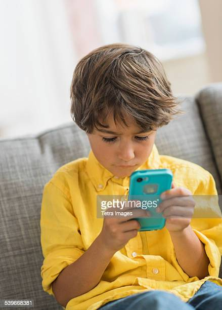 USA, New Jersey, Boy (6-7) sitting on sofa and using cell phone